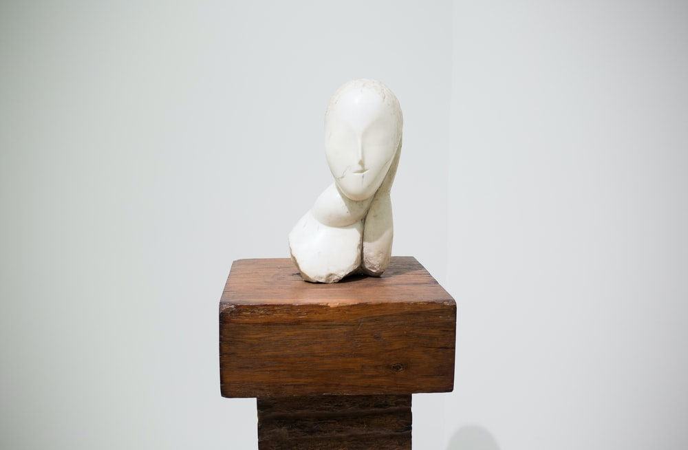 white bust on brown stand