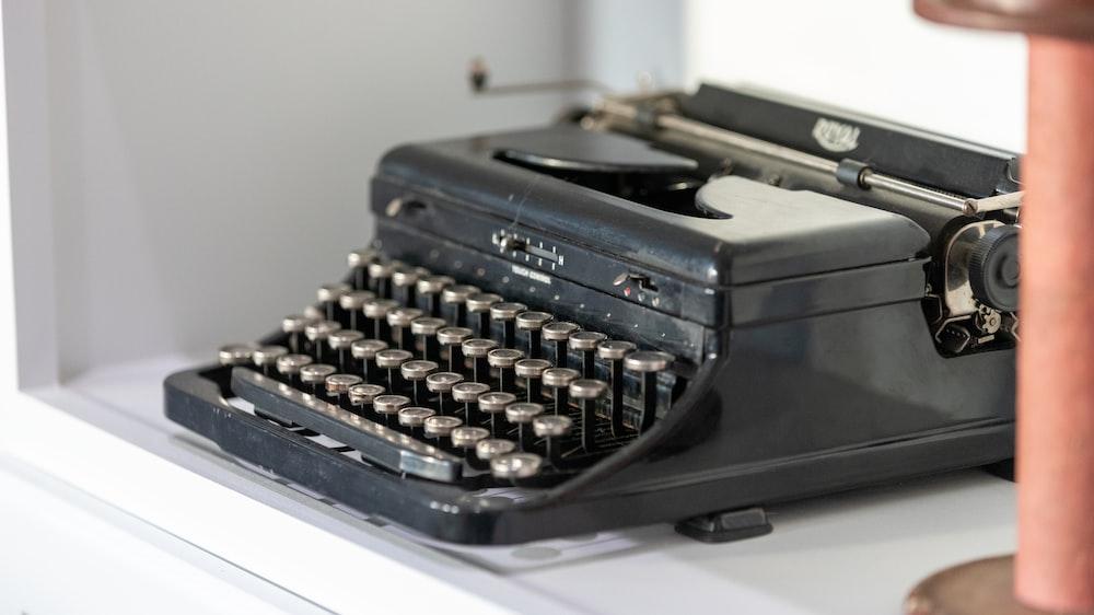 black typewriter beside wall