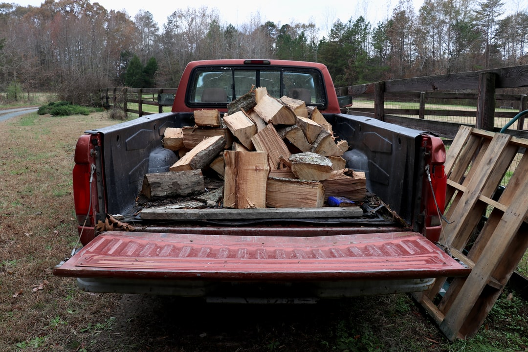 An old pickup truck loaded down with firewood.