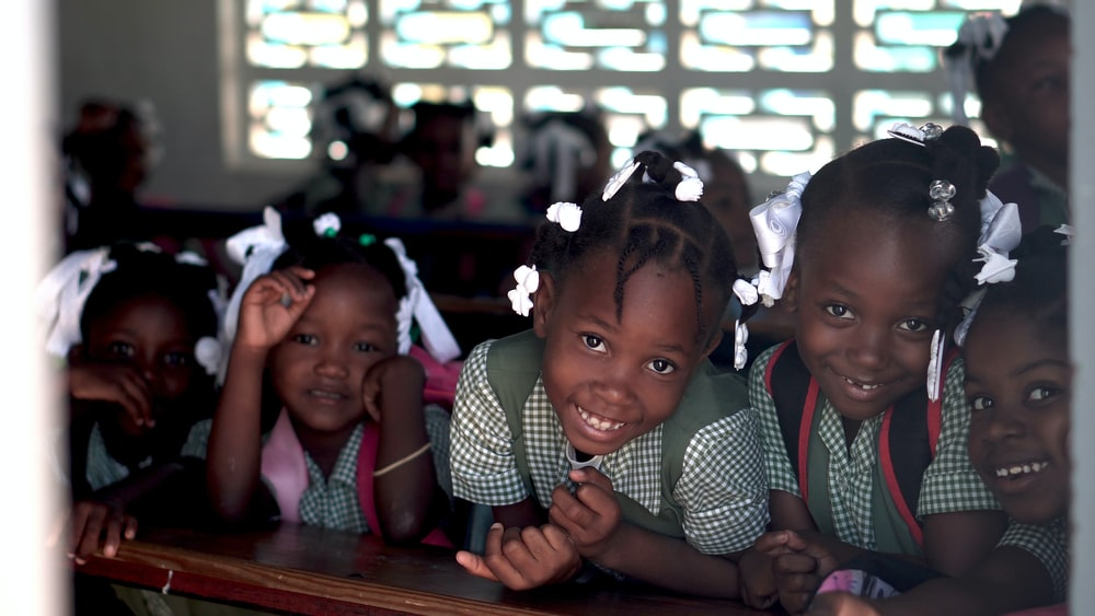 selective focus photo of children leaning on deks