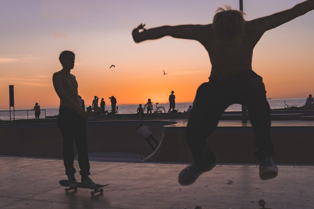 silhouette photography of skateboarders