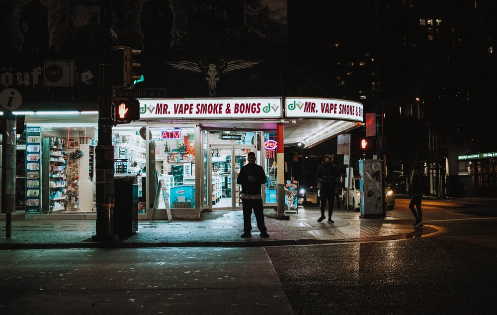 people near store beside road at night