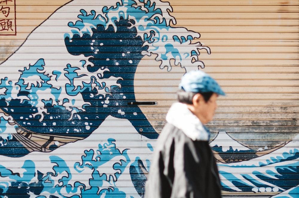 man walking beside The Great Wave Off Kanagawa painting on metal garage door