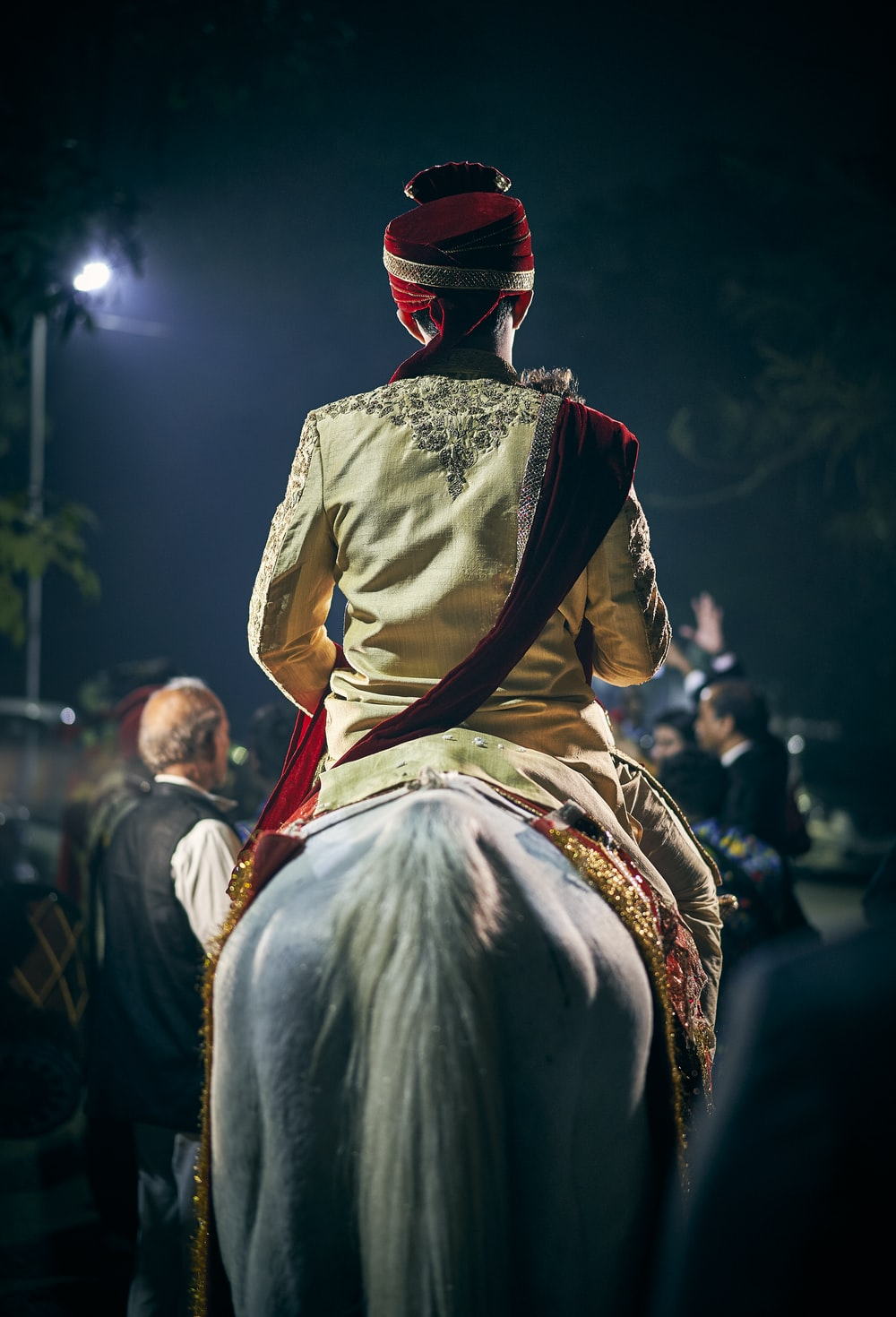 person sitting on horse near people during night