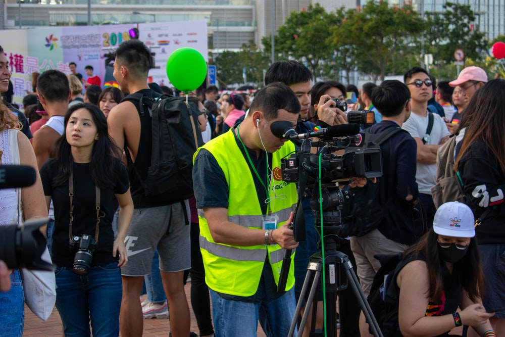 man in green vest using professional video camera