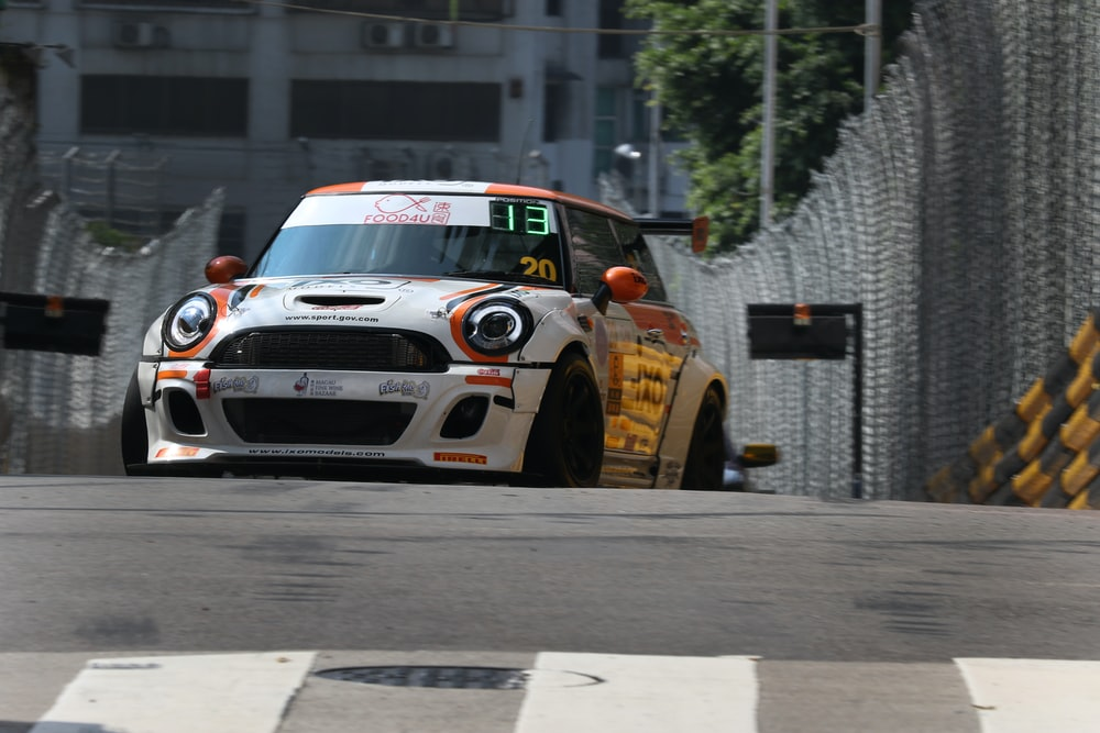 white and red Mini Cooper crossing race track