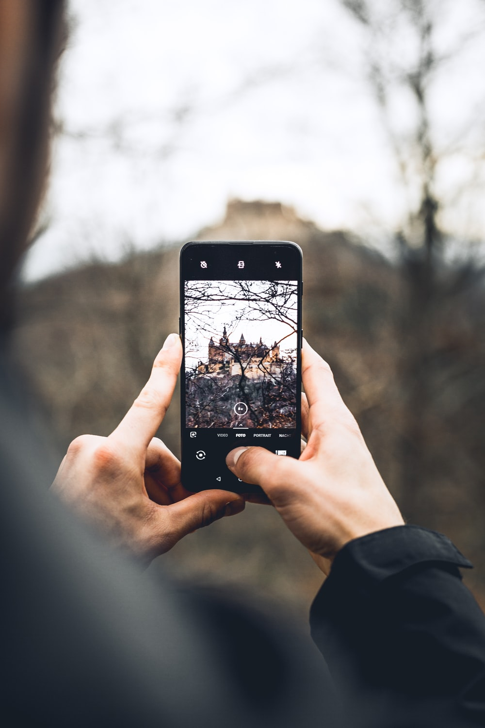 selective focus photo of phone hold by woman displaying bare trees and brown building in distant