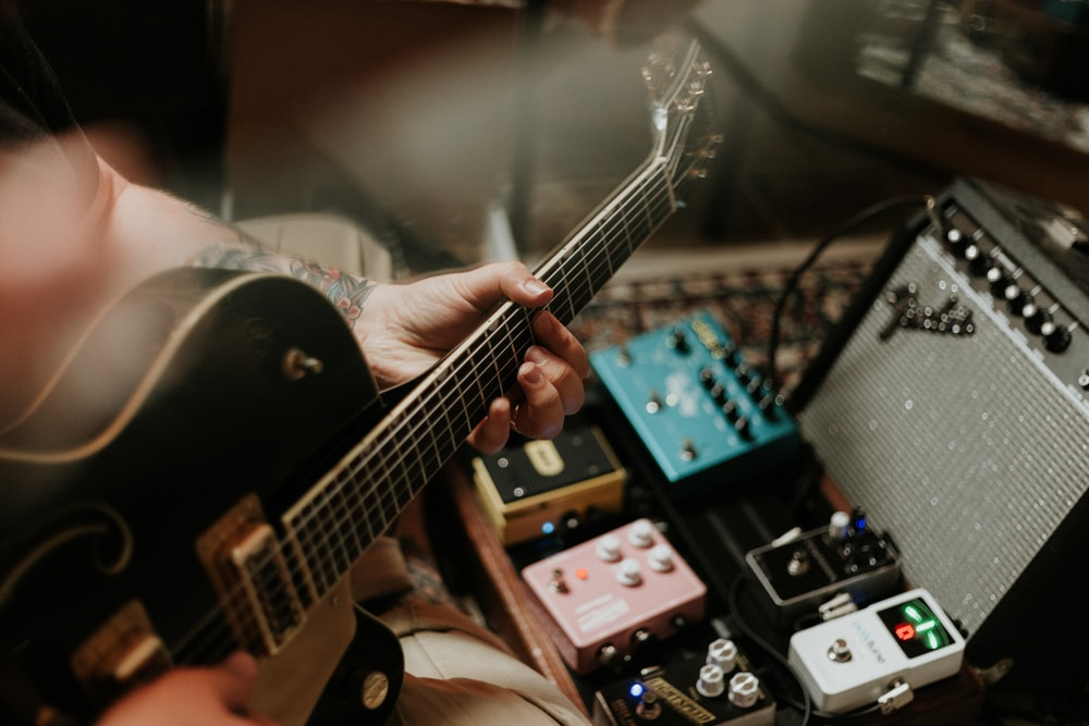 person playing guitar near guitar pedals and amplifier