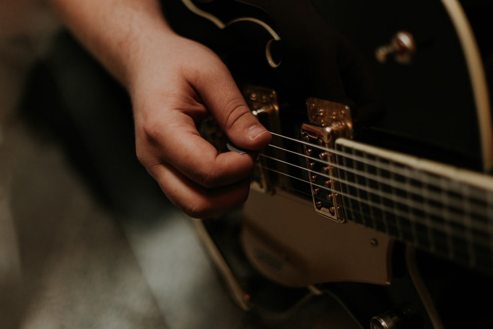 person holding black guitar