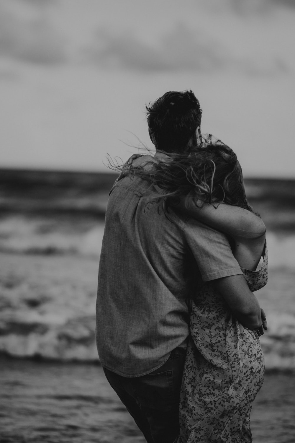 gray-scale photo of man and woman hugging