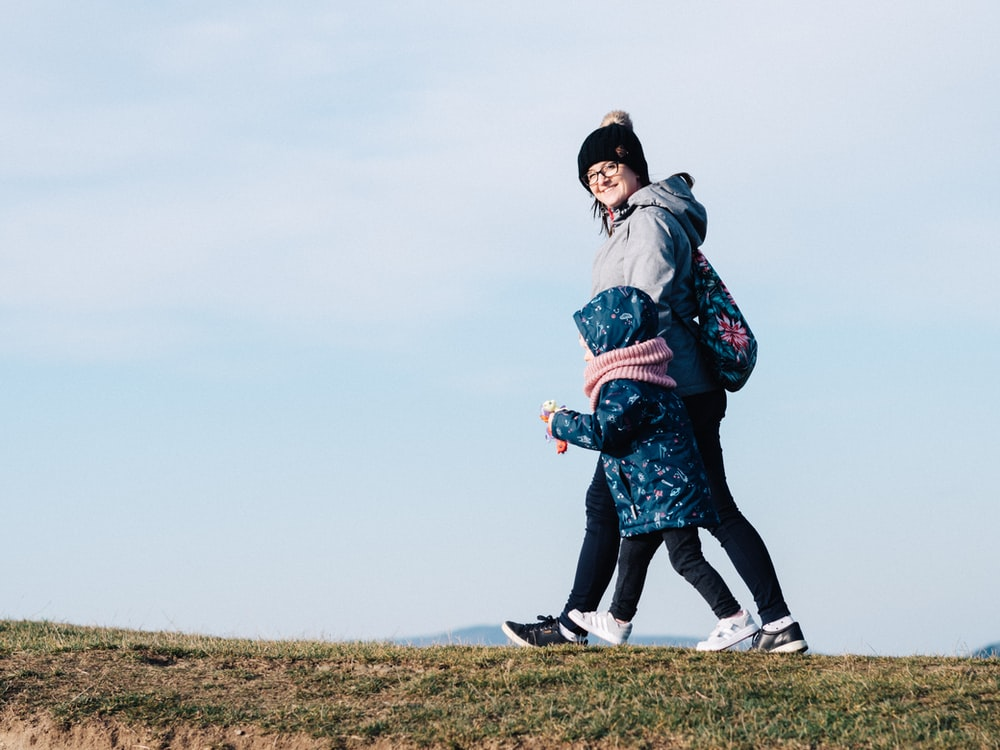 woman and girl on hill