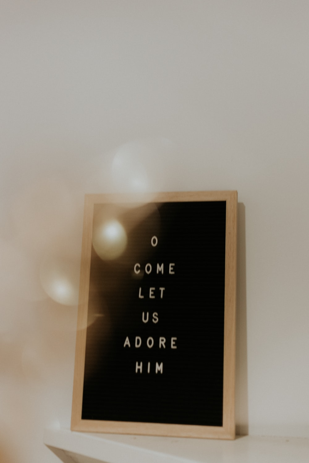 shallow focus photo of come let us adore him quoteboard with brown wooden frame