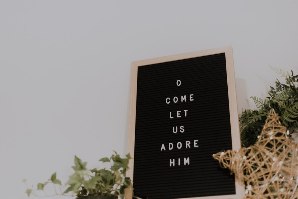 shallow focus photo of come let us adore him quote board with brown wooden frame