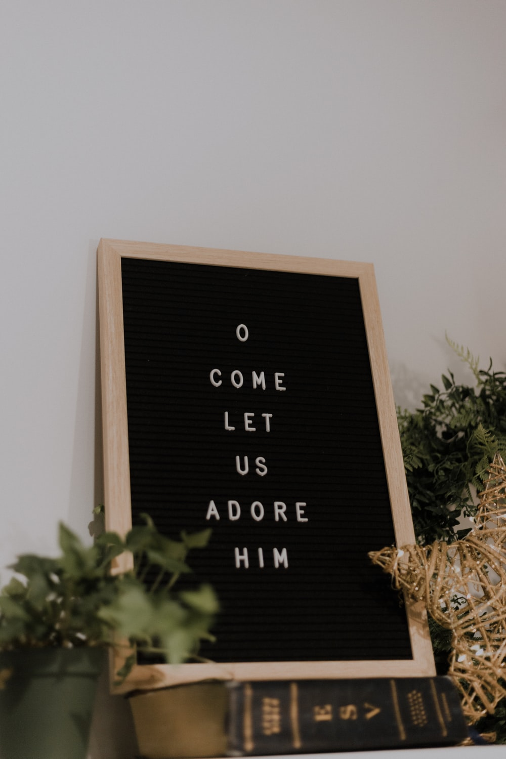 come let us adore him quote board with brown wooden frame