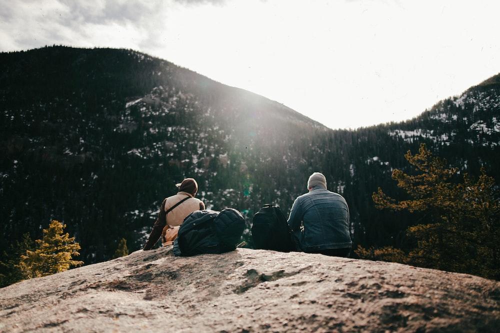 two men sitting on rock