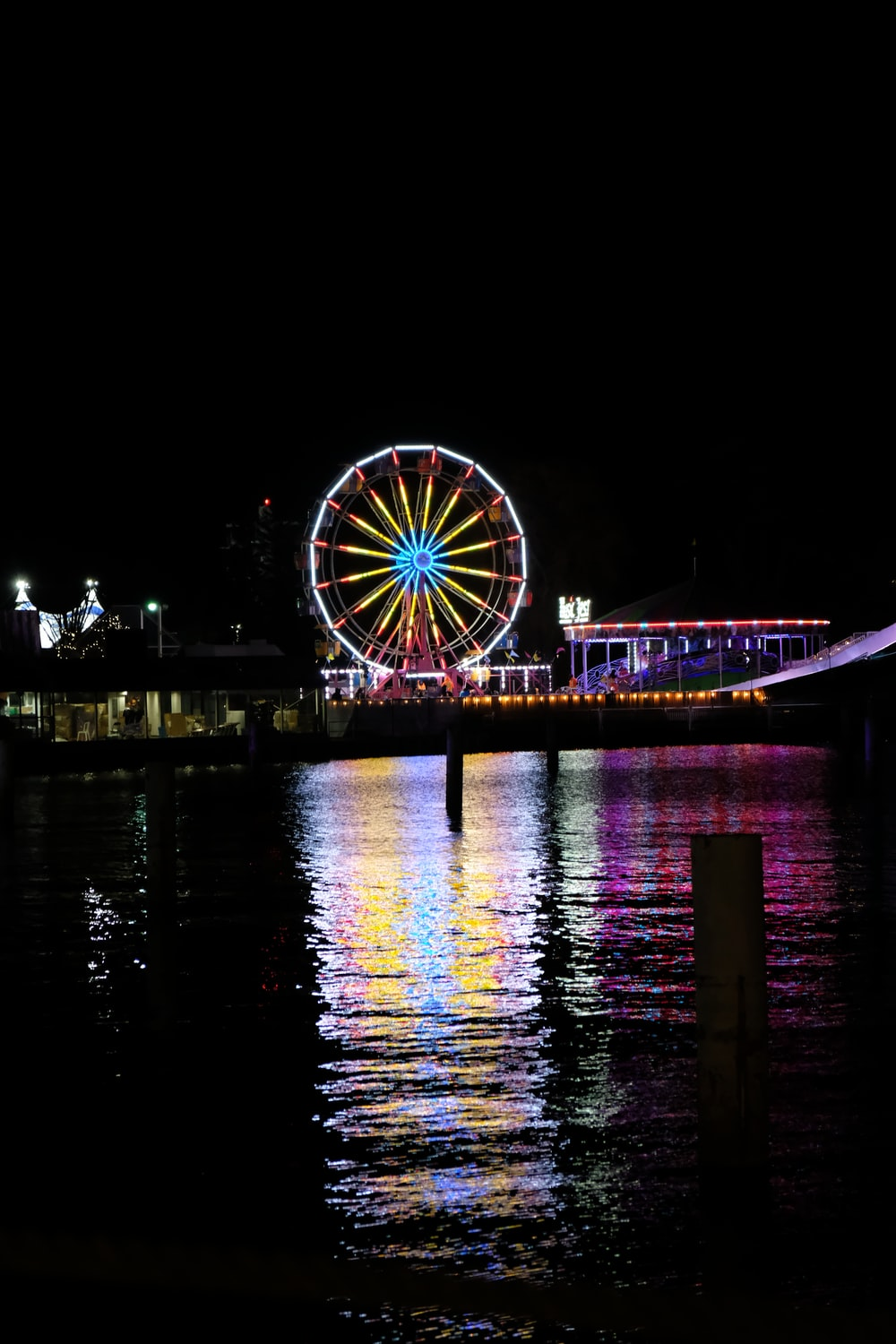 lighted Ferris wheel reflecting on body of water
