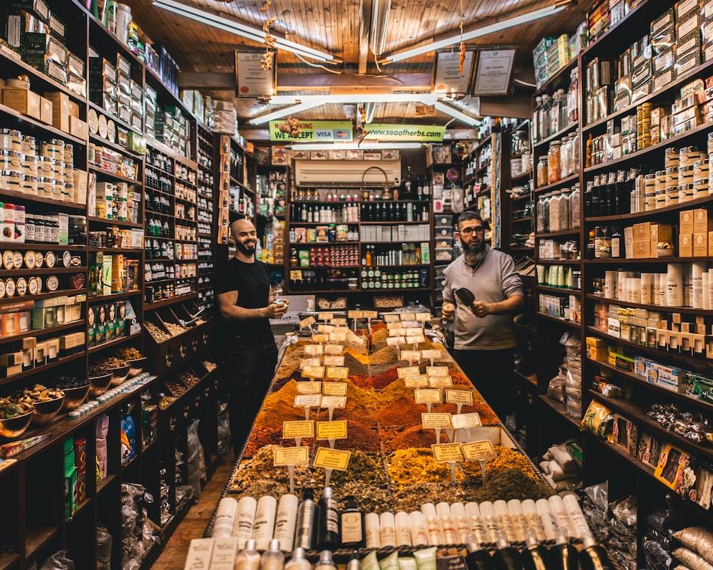 two men standing beside shelves