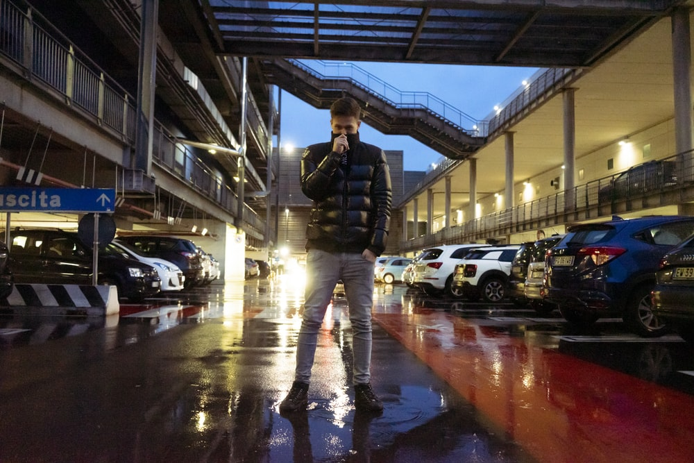 man standing at the parking lot near parked cars