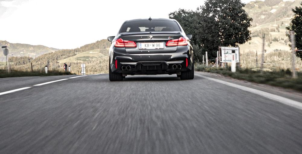 black BMW car on road during daytime