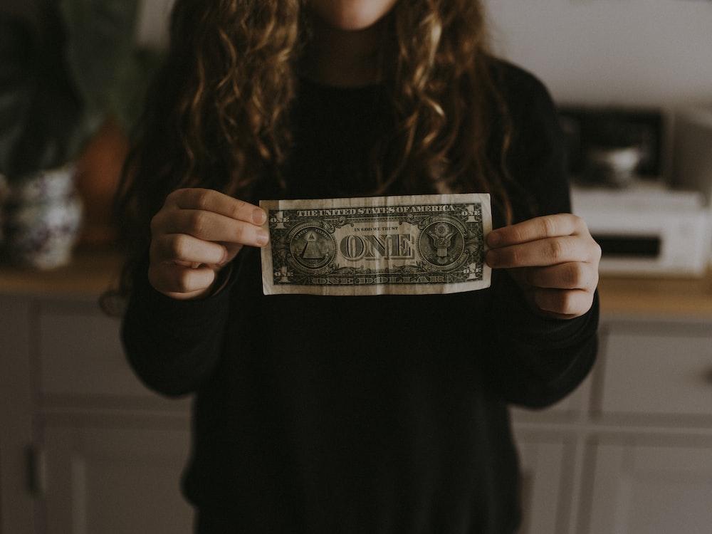 girl holding 1 U.S. dollar banknote
