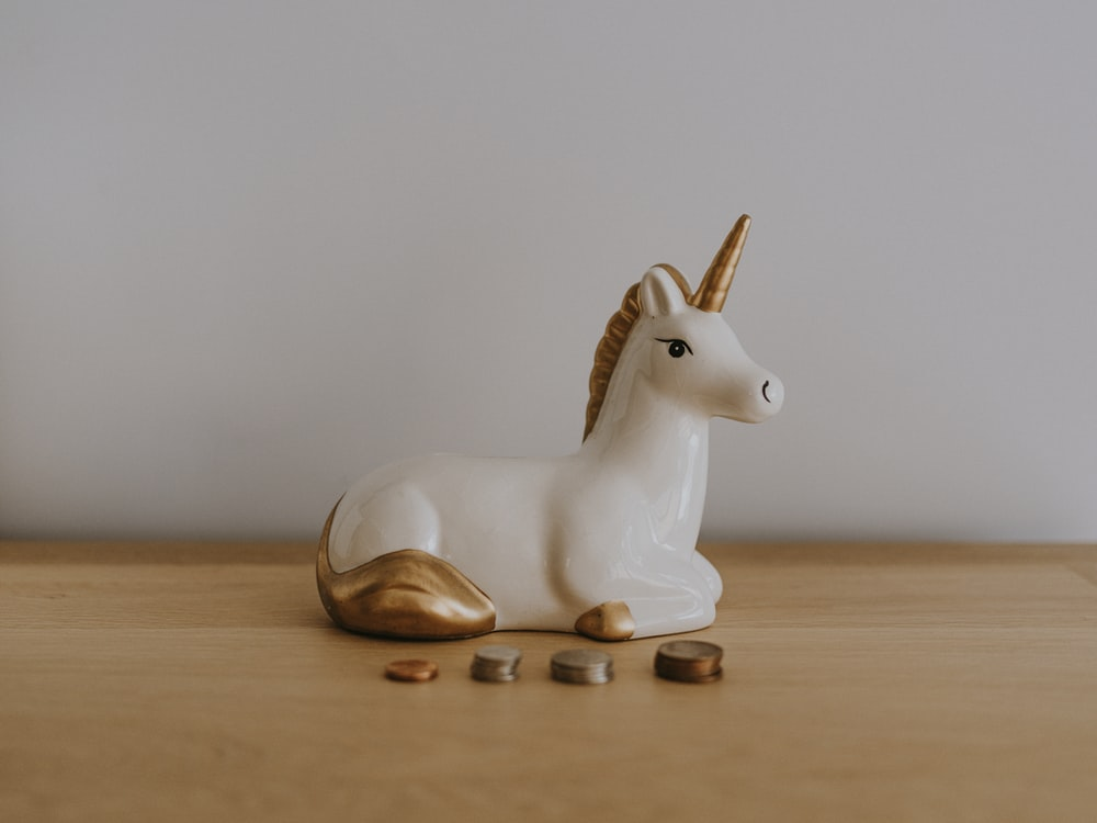 white and gold ceramic unicorn figurine near coins