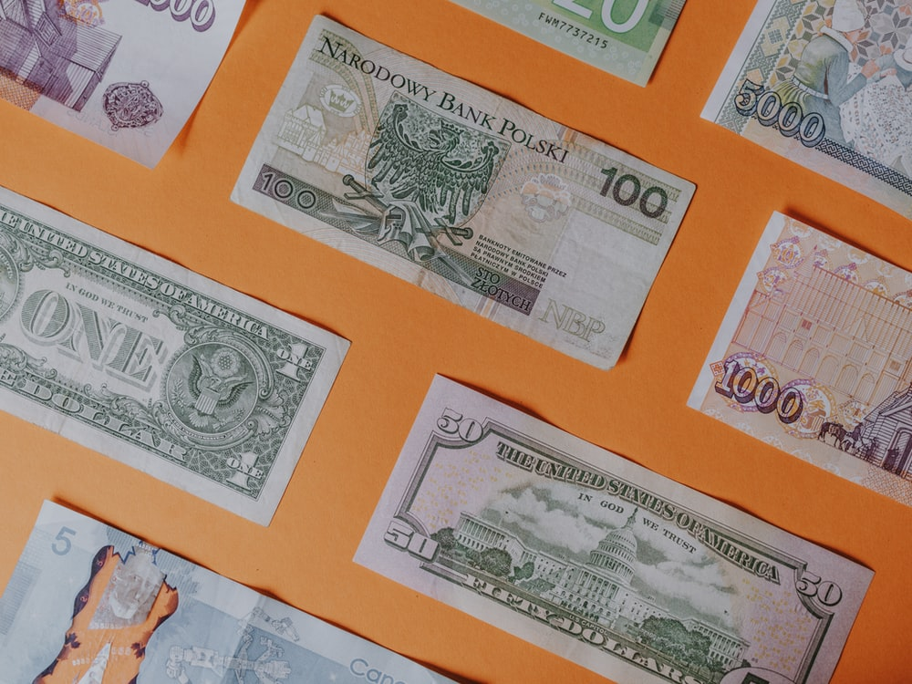 assorted banknotes on orange surface