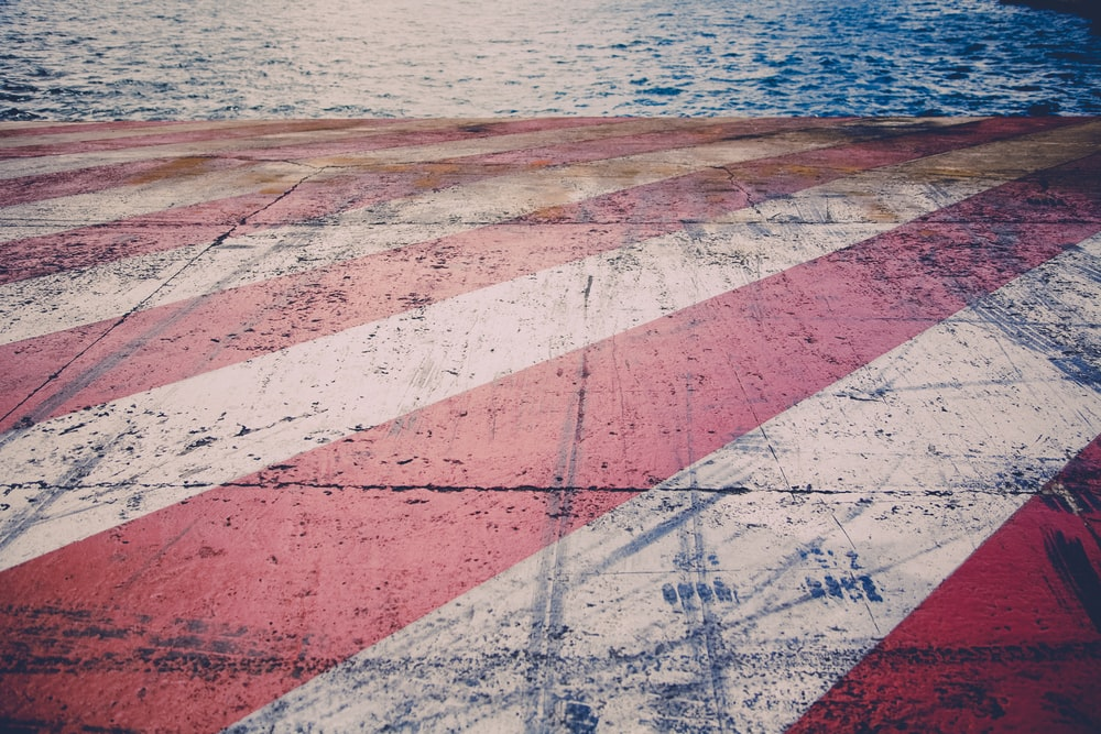 red and white striped painted concrete by body of water