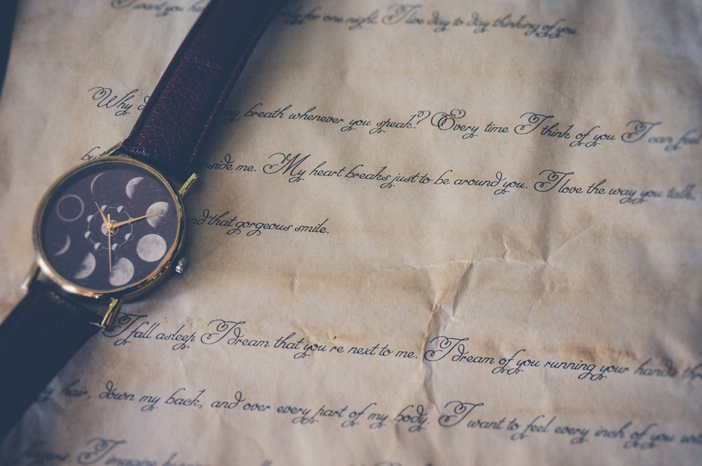 round black and gold-colored analog watch with brown leather band on printer paper