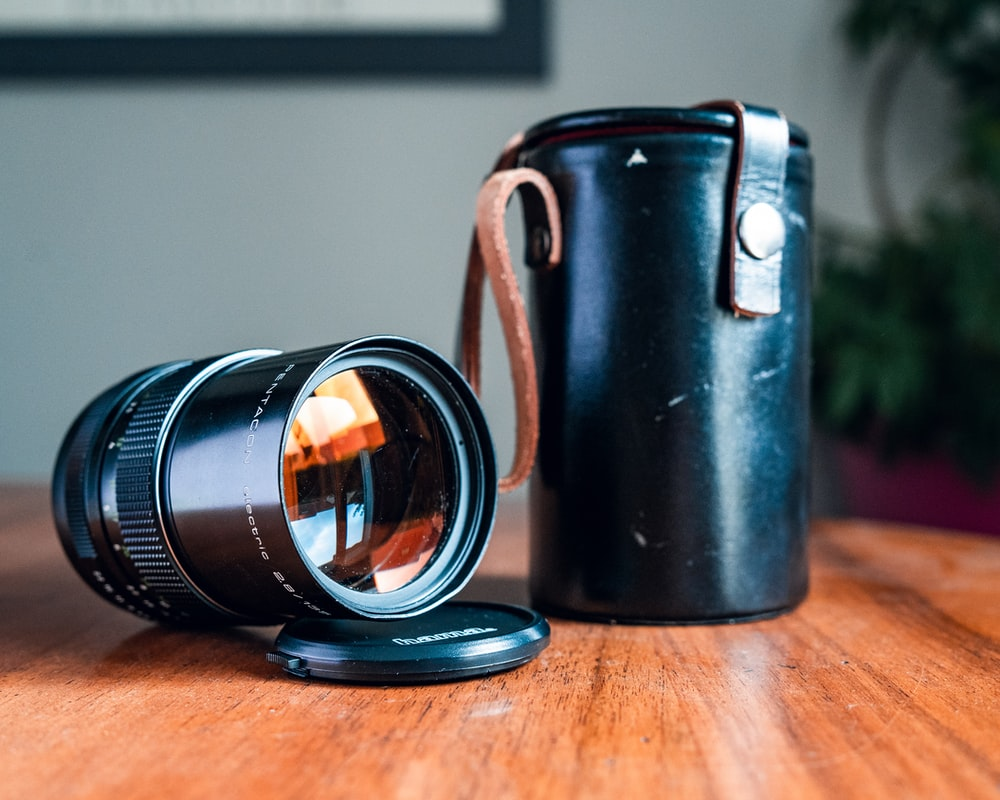 black camera lens with leather case on wooden surface