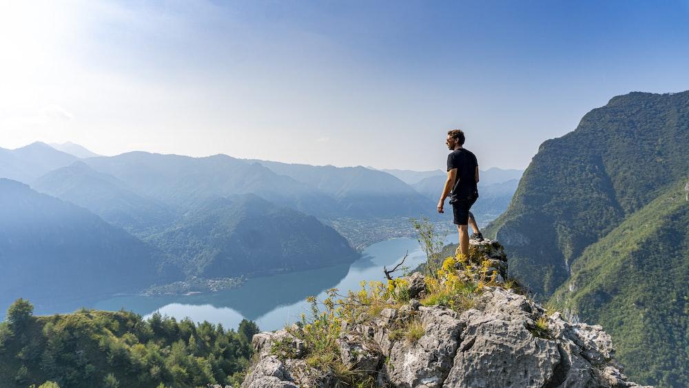 man standing on boulder during daytime