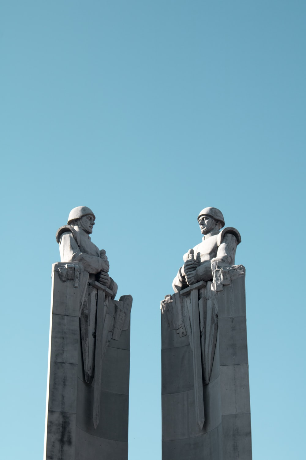 two man themed statues under blue sky
