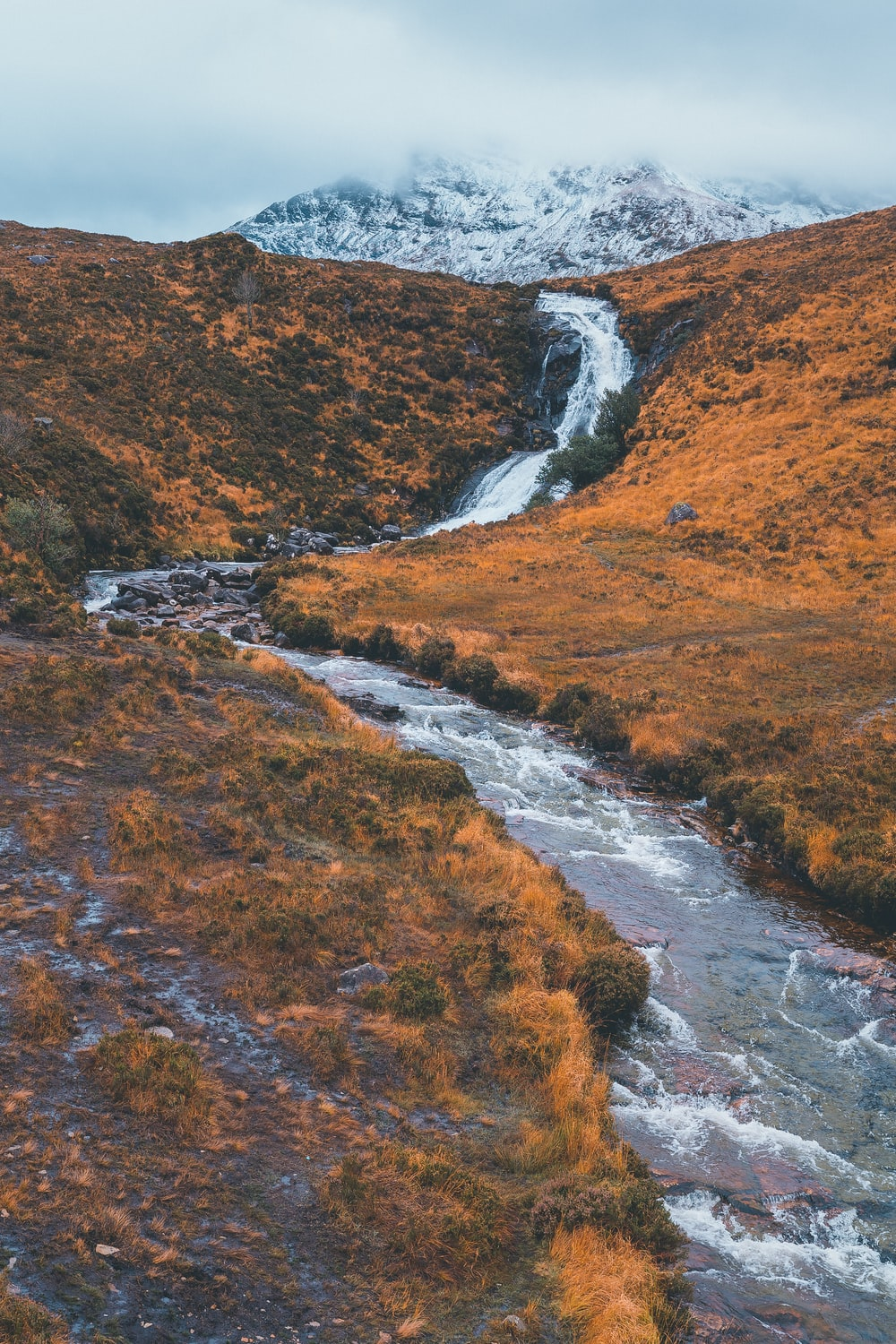 flowing river near field viewing mountain under white sky during daytime