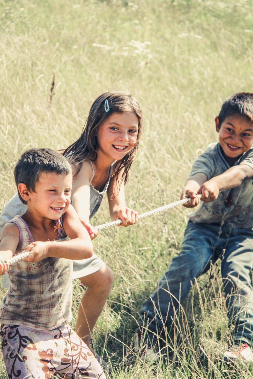 three kids pulling on a rope during daytime