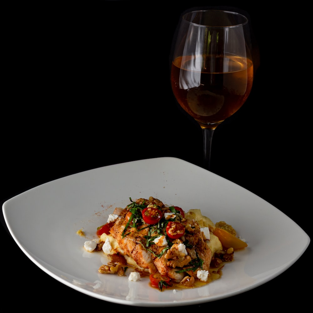 food on white plate beside tulip wine glass