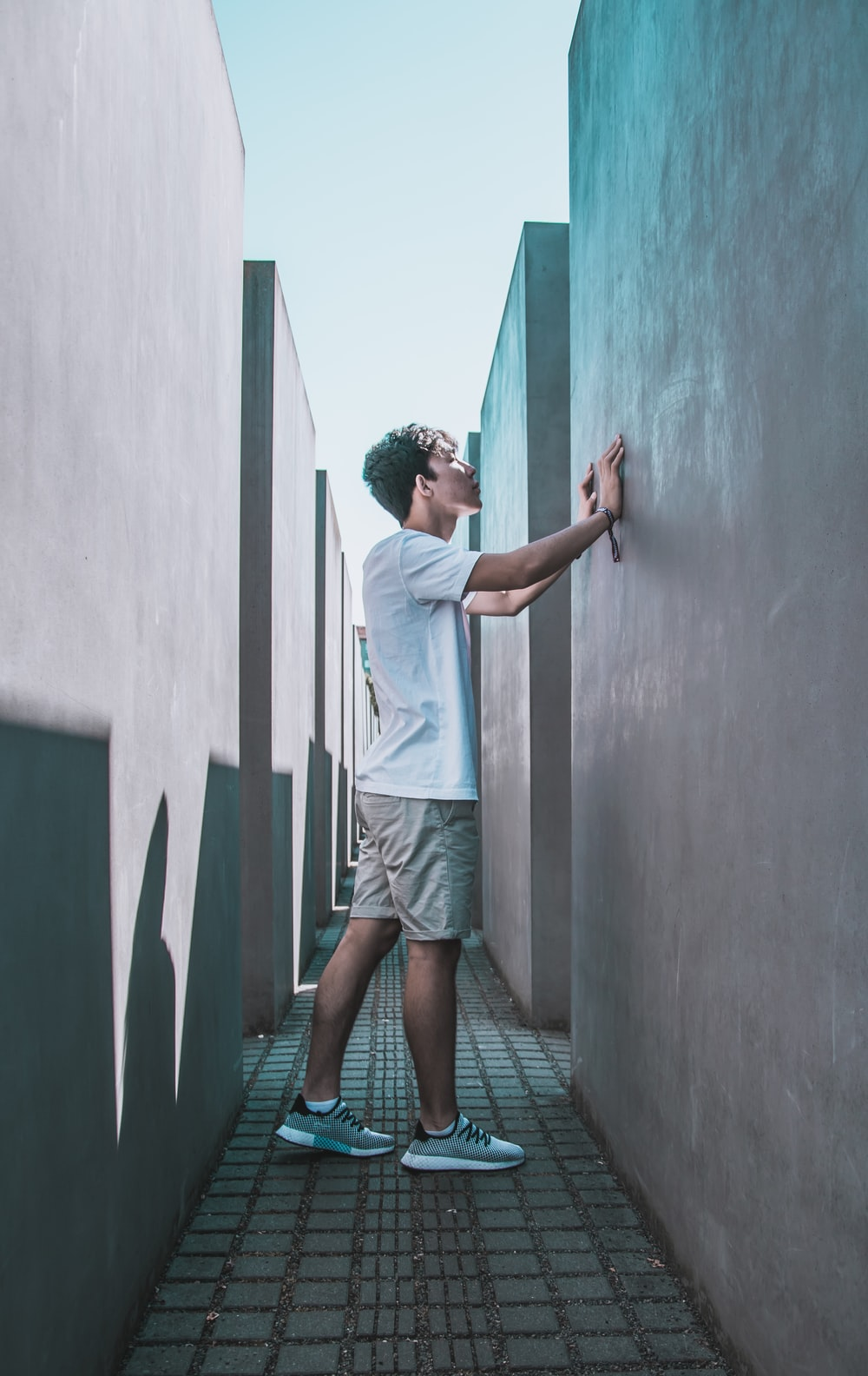 man standing and touching wall