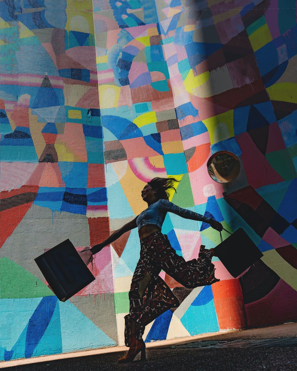 woman holding bag beside mural painting