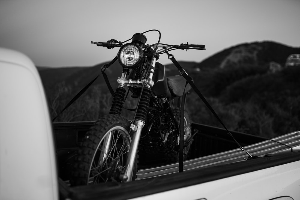 grayscale photography of motorcycle on truckbed
