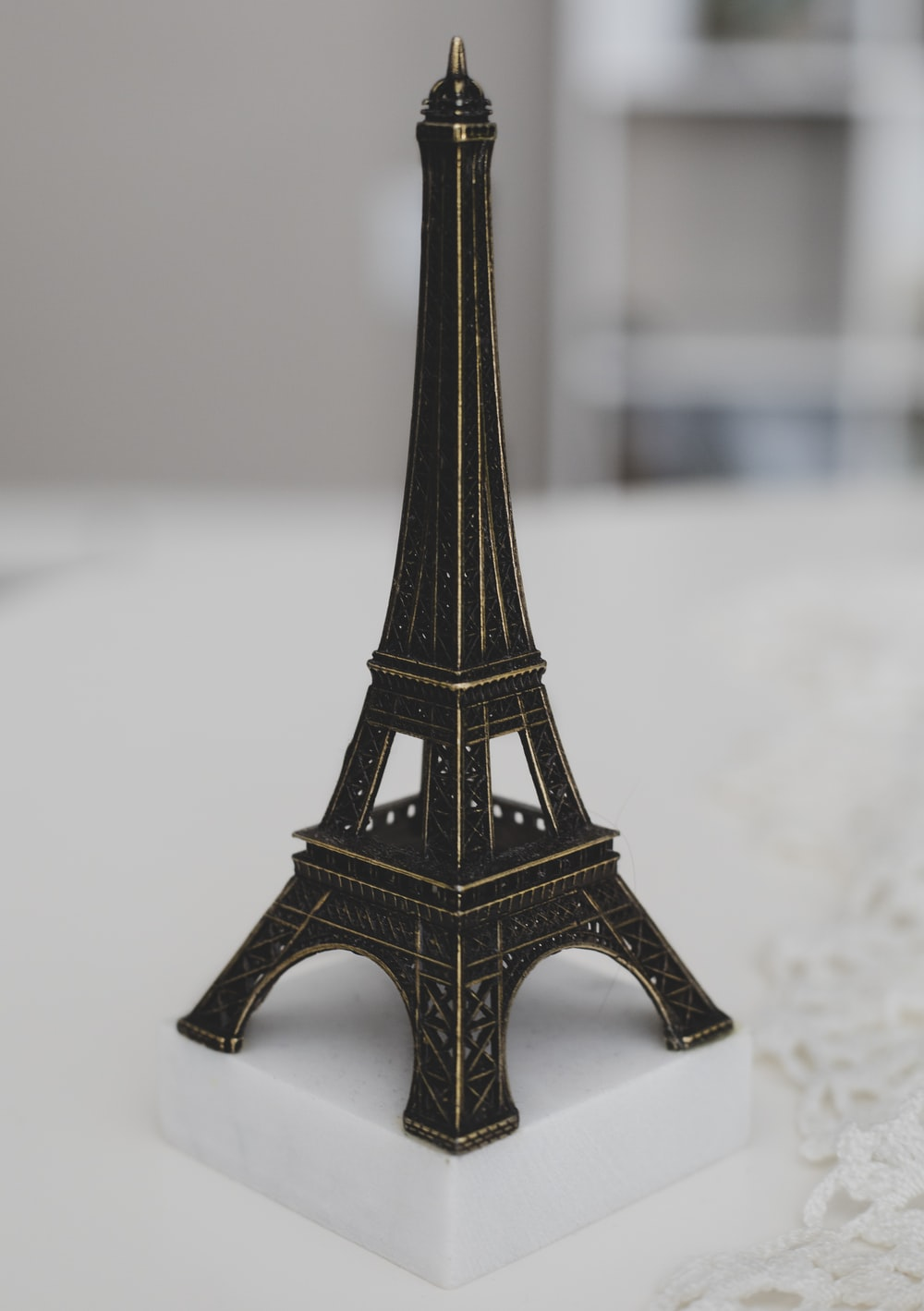 Eiffel Tower miniature on white surface