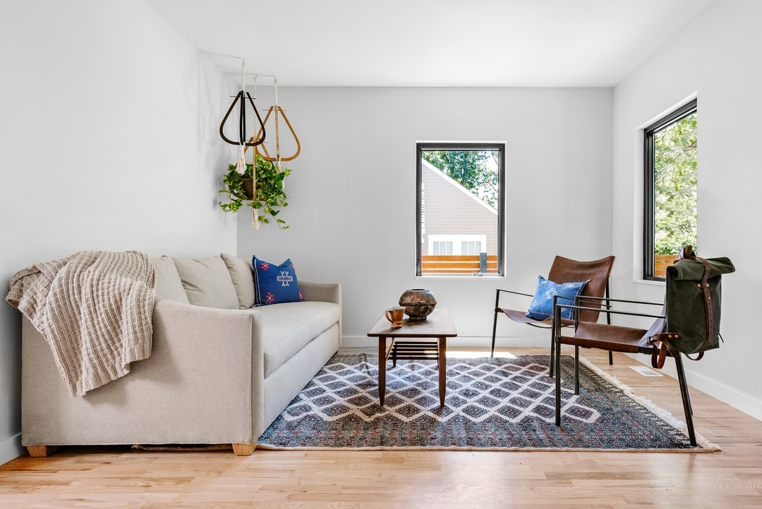 photo of gray couch in front of brown wooden table