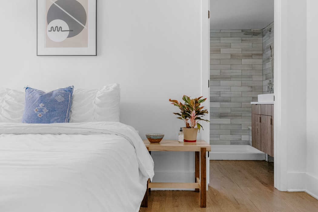 Soft-toned bedroom with natural wooden bedside table