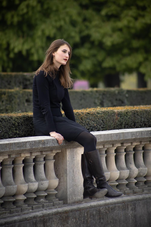 woman wearing black dress sitting on ballast fence