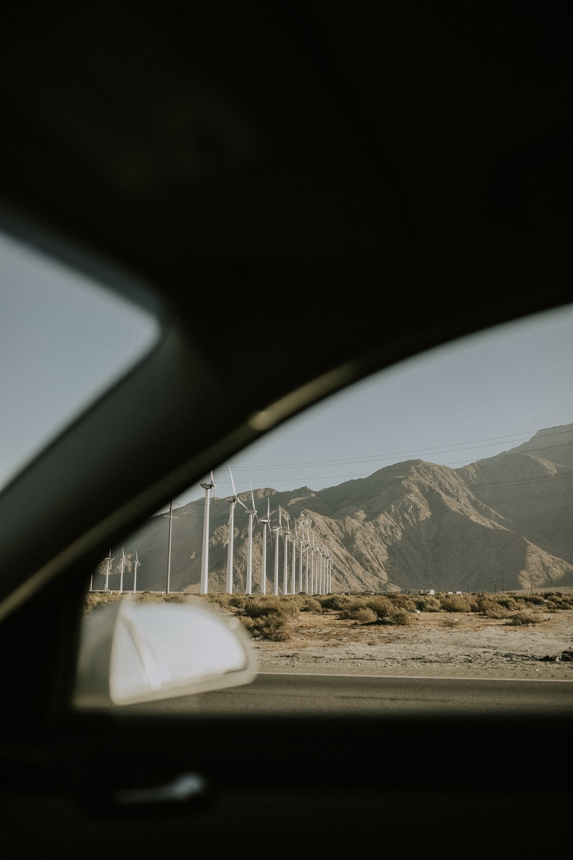 vehicle crossing beside windmill field