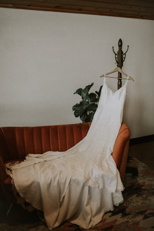 women's white wedding dress hanging on coat rack