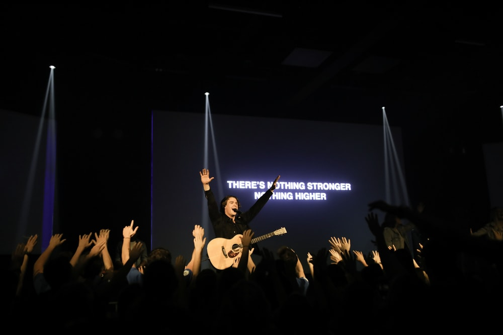 man with guitar raising hands on stage