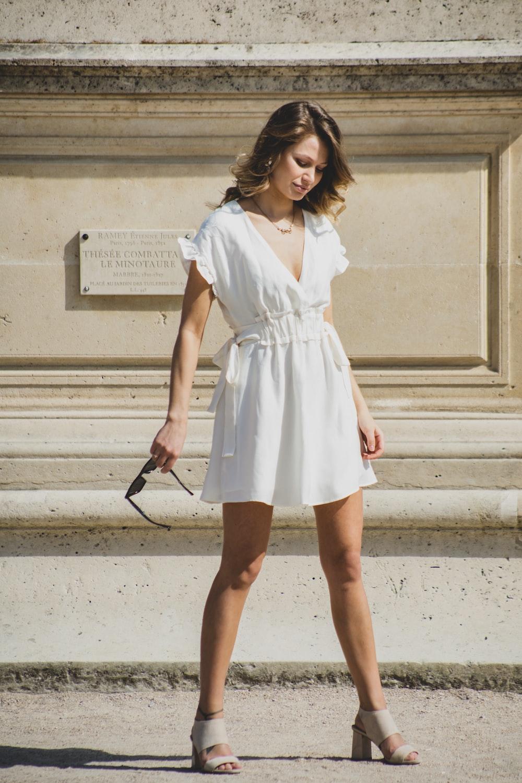woman in white V-neck cap-sleeved mini dress standing near wall