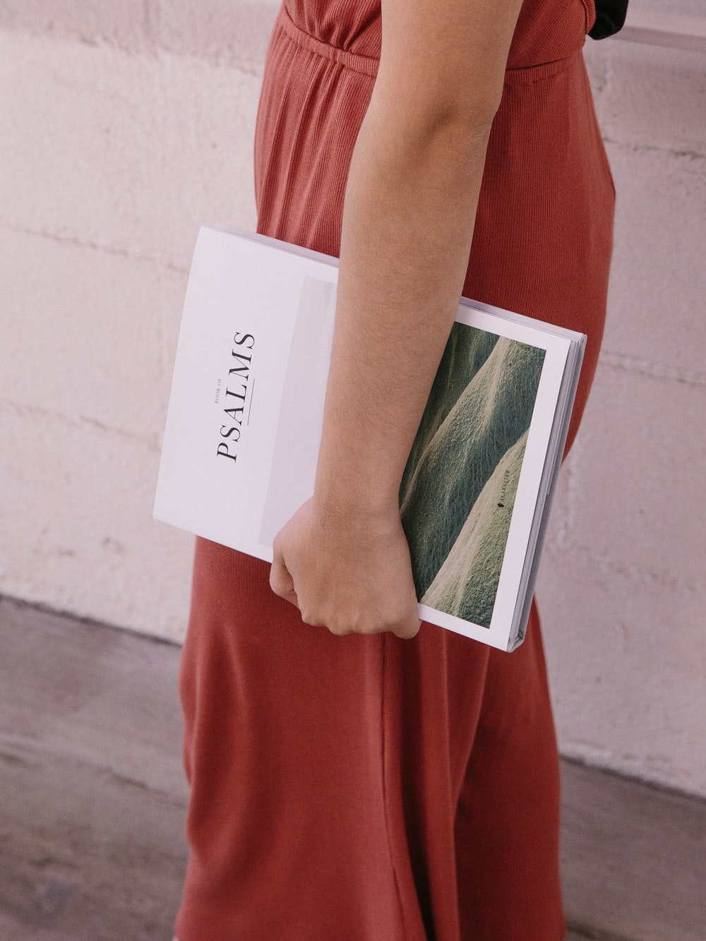 woman wearing red jumpsuit holding Psalms book