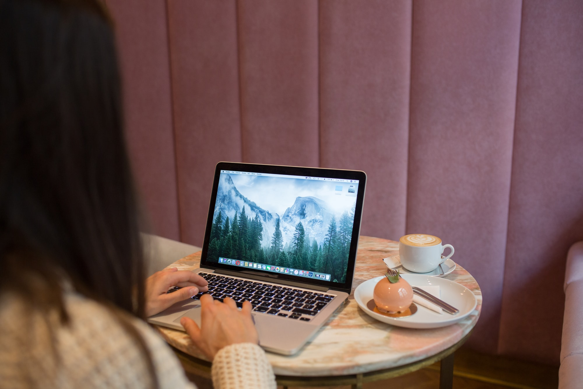 Female hands typing on MacBook pro in a pink cafe. Lunchtime break.