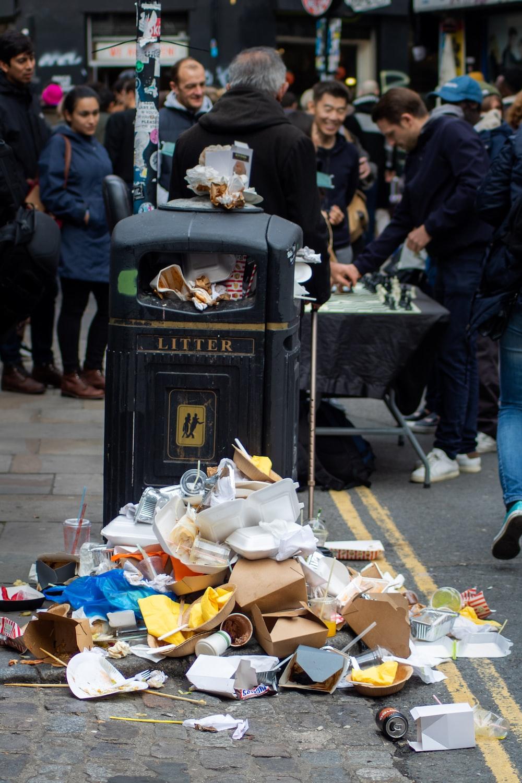 person standing beside garbage bin