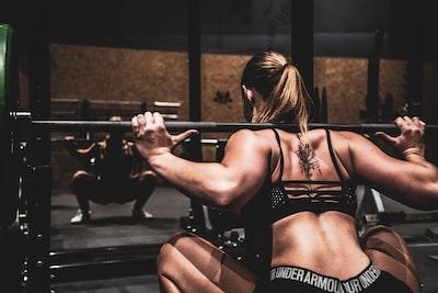 ジムでスクワットトレーニングする女性の画像