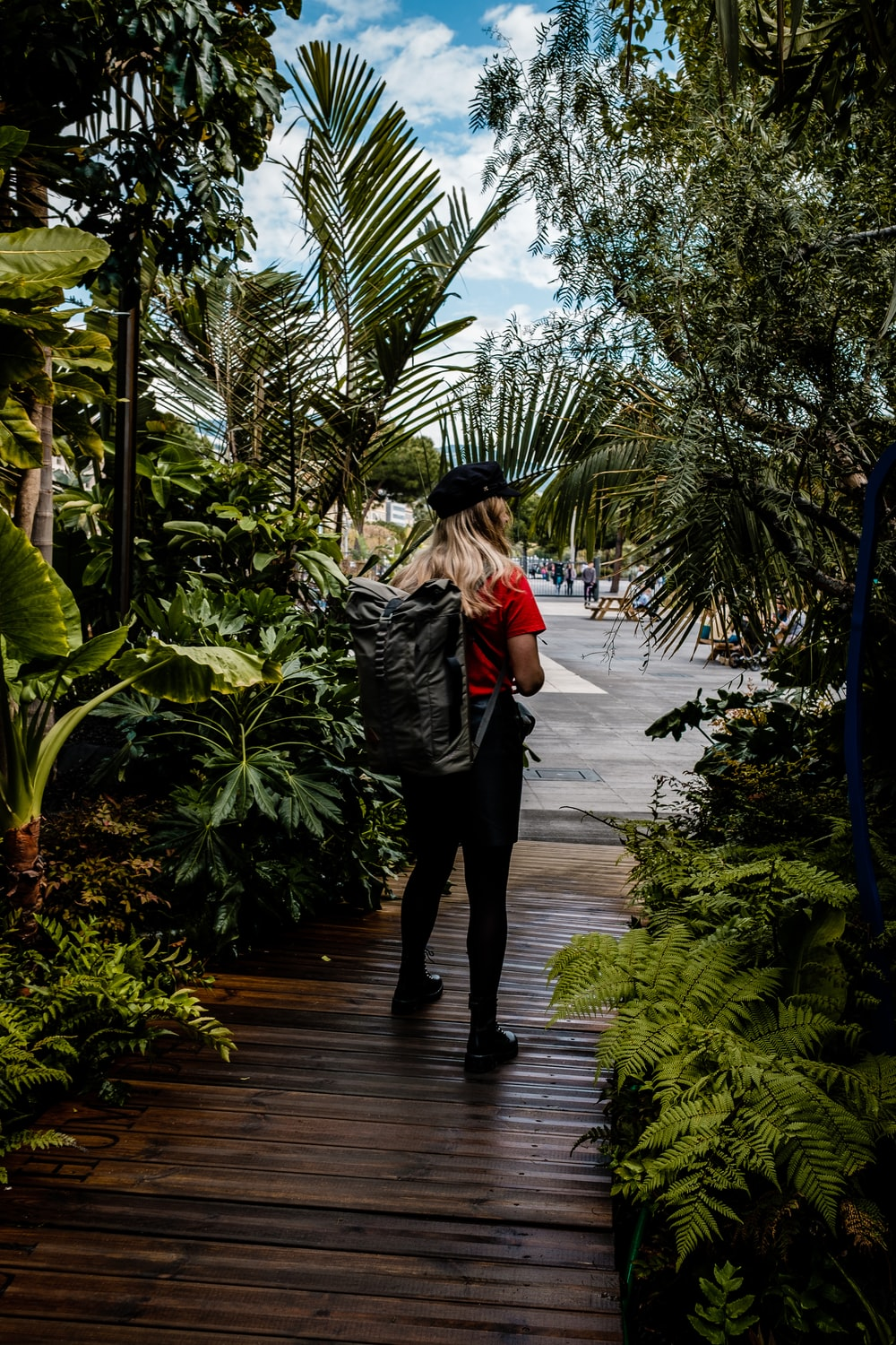woman standing on footbridge surrounded by plants